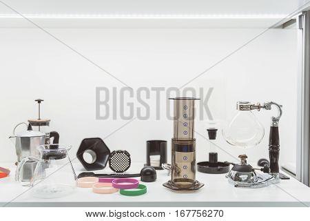Metal teapot is near glass bowl. Modern flask beside brown beaker at white surface