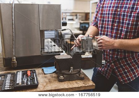 Man is holing spare part of coffee apparatus is on lathe. Case with tools at board