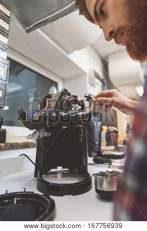 Concentrated man is looking at broken apparatus for coffee-seeds