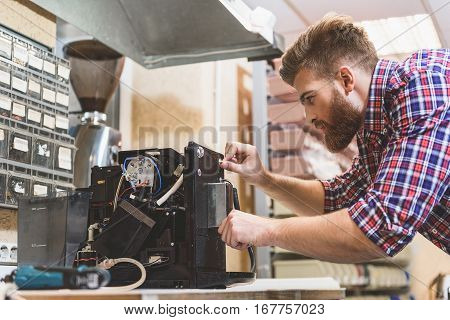 Concentrated male person is looking at fractured apparatus for coffee-seeds. He trying to solve problem