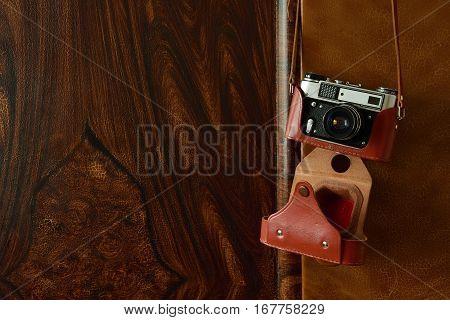 Vintage rangefinder camera hung on the door of a retro wardrobe.
