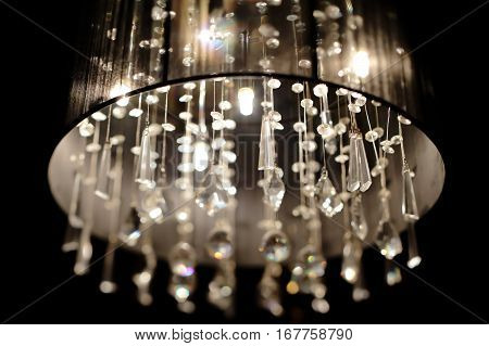 Chrystal chandelier close-up. Glamour black and white background with copy space. Selective focus