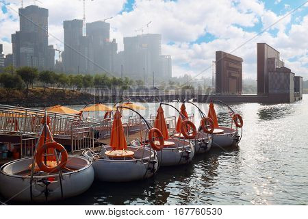 Rows of circle promenade motor boat at rest with man in one and construction buildings aback in Seoul