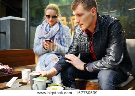 Woman looking in smartphone and man drinks on bench in cafe in Seoul, focus on man