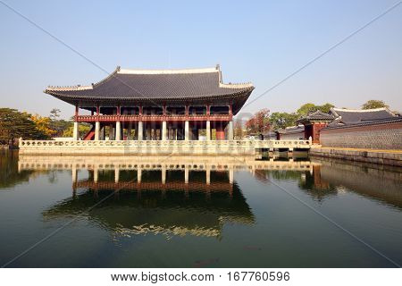 Beautiful single-level pagoda on lake among trees in Gyeongbokgung, Seoul
