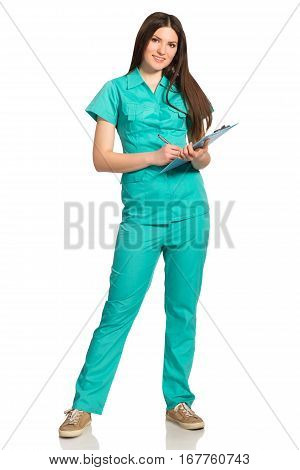 Relaxed smiling nurse in uniform with clipboard writing isolated on white background