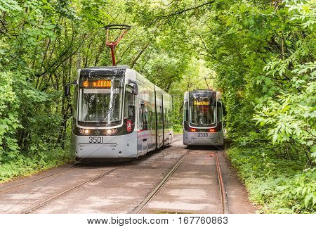 Moscow Russia - July 8 2016: City tram goes among the green thickets of trees.