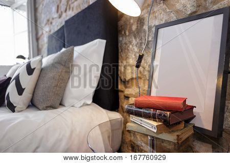 Glass Nightstand With Old Books and Empty Photo Frame