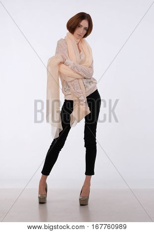 She dressed on elegant lace blouse and translucent beige shawl on the shoulders. She looking forward. Hands near chest.