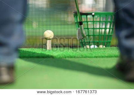 Man hitting ball for golf during training, focus on ball, shallow dof, noface