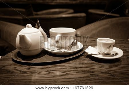 cup of coffee and tea on bar table, sepia toned