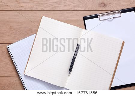 Notepad and personal diary or organizer with pen. Office or student's devices on modern wooden desk. Working table top view. Education or job background with copy space on paper sheet
