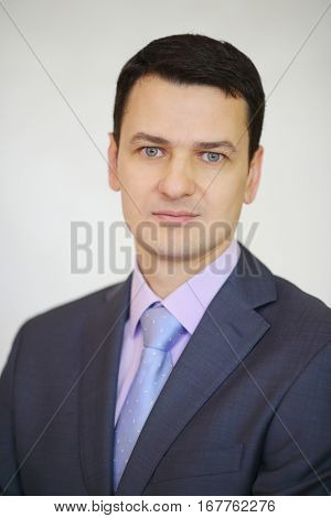 Serious elegance brunet man in suit poses next to white wall in studio