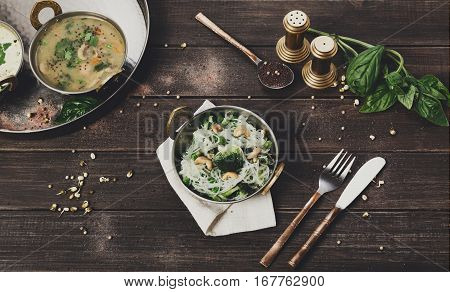 Vegan and vegetarian dish, spicy rice vermicelli with broccoli and cashew in bowl. Indian cuisine with herbs, healthy meal closeup on wood background. Eastern local cuisine restaurant food.