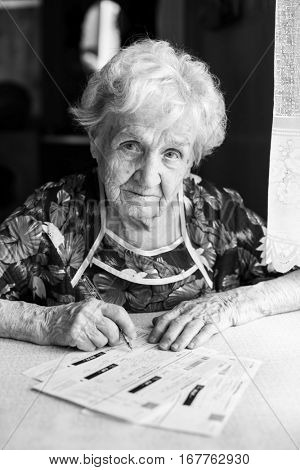An elderly woman with a pen and receipts of utility bills. Black-and-white photo.