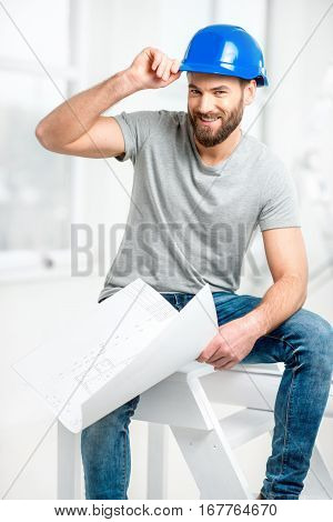 Portrait of a handsome builder, foreman or repairman in the helmet sitting with drawings on ladder in the white interior