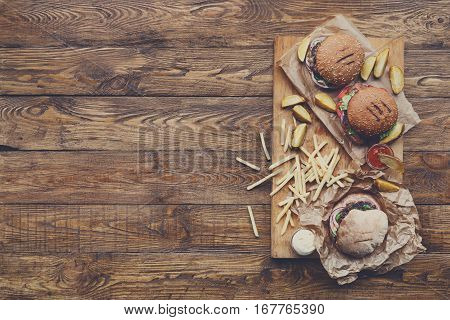 Fast food dish top view. Appetizing meat burgers, potato chips and sauces. Takeaway composition. French fries and hamburgers on wood with copy space. Menu or receipt mockup