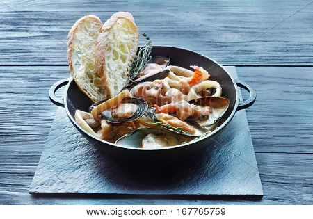 Seafood Stew in Saucepan. Authentic italian restaurant cuisine, healthy delicatessen food. Oysters, shrimps, calamari in white cream sauce with bruschetta. Bowl on dark black wood background
