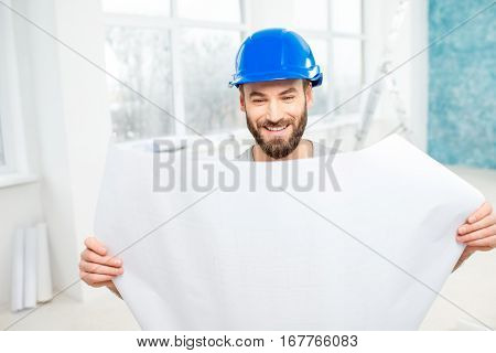 Portrait of a handsome builder, foreman or repairman in the helmet looking at the paper drawings in the white interior