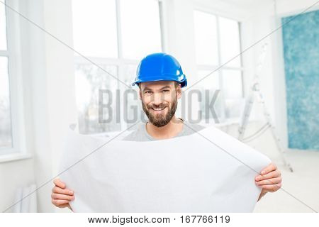 Portrait of a handsome builder, foreman or repairman in the helmet with paper drawings in the white interior