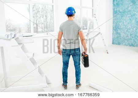 Foreman or worker in uniform with instruments standing back in the white interior during the renovation