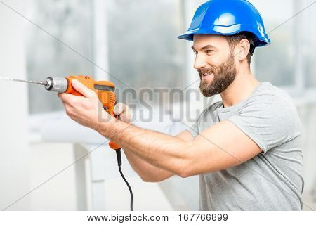 Handsome repairman in protective helmet drilling the wall indoors