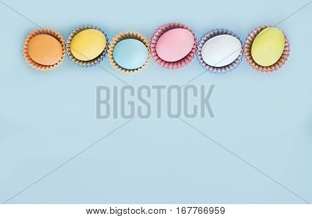 Flat lay row of colorful eggs on a light blue background. Pastel colors vintage card. Negative space for text