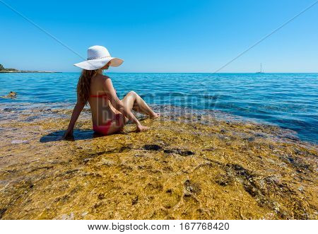 Young woman on the coast of the island. Portrait of a girl in white hat looking at the sea. Beautiful Summer sea side with turquoise water. Cyrpus island, Protaras. View from behind