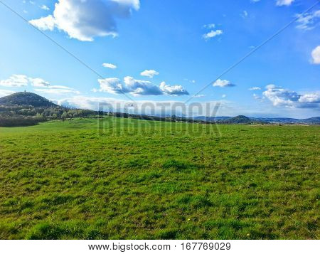 The meadow with nice blue sky with some little clouds by sunny day. The Czech nature. Hills in the background.
