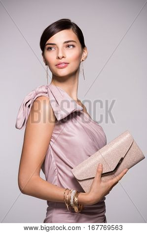 Young beautiful woman in elegant pink dress holding clutch and looking away. Fashion chic woman with purse ready for party. Portrait of elegant girl with luxury accessory isolated on background