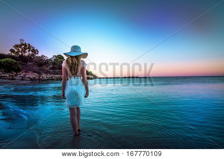 Woman walking down the beach at sunset. Beautiful Sunset sea view in Cyprus island
