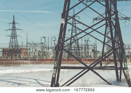 high voltage power lines. electricity distribution station. high voltage electric transmission tower on winter landscape