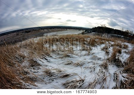 Autumn meets winter. The grass-strewn snow. Sunset sky. Wide angle. Snow field.