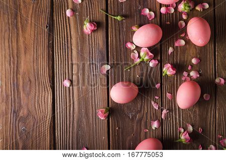 Pink easter eggs on wodden background. Pink eggs and roses. Easter photo concept