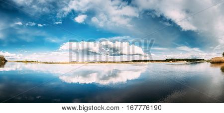 Panorama Of River Or Lake Landscape With Reflections Of Cloudy Sky In Water. Ripple Surface Of Calm Water At Evening Or Morning Time. Forest On Other Side. Nature Of Eastern Europe
