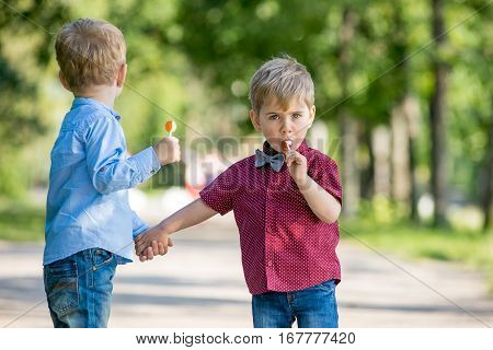 Little blond boy walking in the park with a friend in the spring are on the road with candy in his hands.