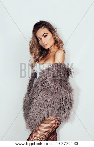 people beauty and lifestyle concept - young beautiful brunette with curly hair in a beautiful fur coat and tights in the mesh and pink underwear a gray background. Club style.