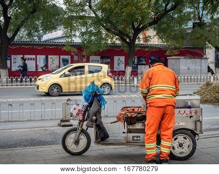 Beijing, China - Oct 30, 2016: Back of a roadside cleaner on Wangfujing Street, Dongcheng area. Chinese characters on uniform mean
