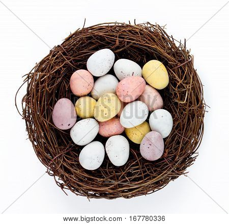 Easter basket nest with Easter candy eggs isolated on white background - Easter treat for kids and element festive Easter decor