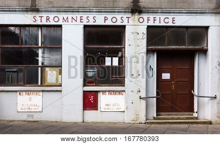 Orkneys Scotland - June 5 2012: The facade and entrance of the non-maintained local Post Office. LIght gray paint brown door and dark windows. A few sign in red on white.