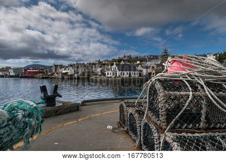 Orkneys Scotland - June 5 2012: The skyline of Stromness downtown seen from the docks with a stack of lobster traps up front. Blue cloudy sky. Reflecting sea water and big black mooring post.