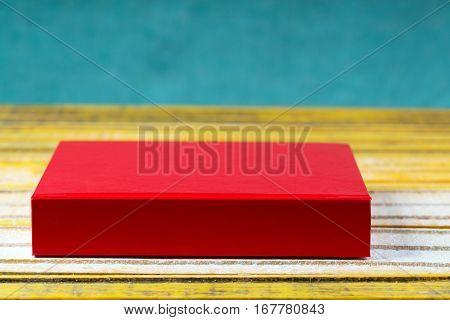 Red hardcover book on wooden table. Back to school. Copy space.