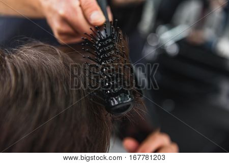 Close up of hairdresser hands using hairdryer and comb for making hairstyle
