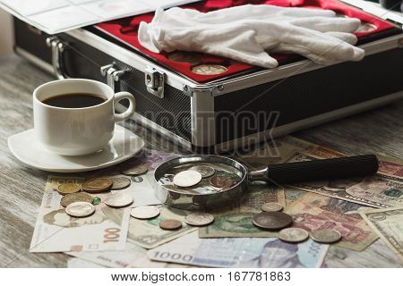 Different collector's coins and banknotes with a magnifying glass box for coins and cup of coffee soft focus background