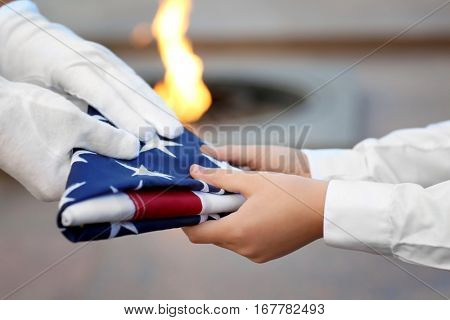 Hands holding folded American flag on Eternal flame background