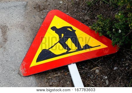 Closeup of roadwork sign lying on the ground.