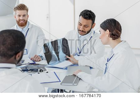 Serious young man is looking at x-ray photo pensively. Male doctors are sitting at table near her
