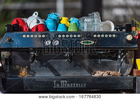 Sydney Australia - July 23 2016: La Marzocco industrial grade coffee machine with bright colorful cups and glasses in outdoors cafe in Sydney CBD