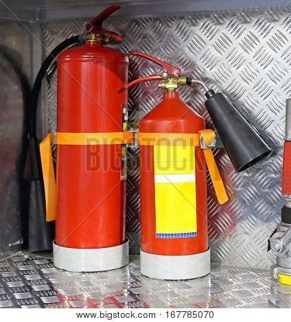 Two Red Fire Extinguishers in Truck Compartment
