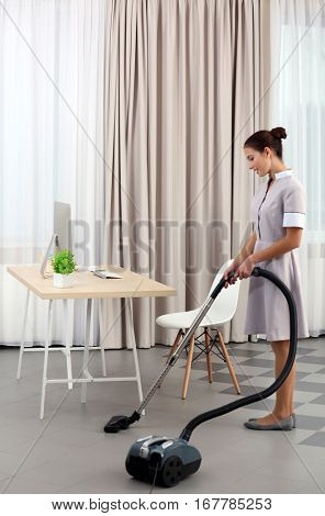 Female chambermaid with vacuum in hotel room